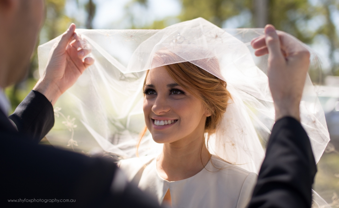 Lifting the veil of a smiling bride